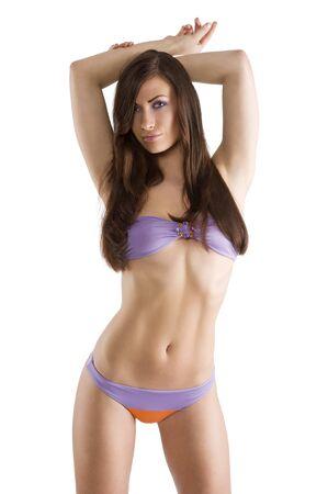 sexy en mooie brunette vrouw in paarse zwembroek bikini en lange haren in de camera kijken  Stockfoto