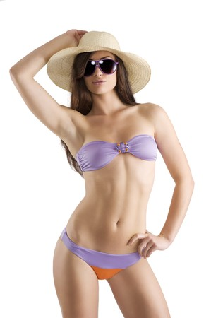 sensual beautiful brunette with long hair wearing a bikini swimsuit hat and sunglasses isolated on white