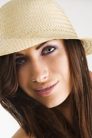 closeup portrait of pretty brunette woman wearing a nice summer hat with long hair photo