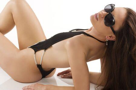 chica sexy Morena con pelo largo, vistiendo un traje de ba�o negro y gafas de sol que se establecen en blanco  Foto de archivo - 7337251