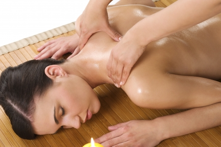 attractive beautiful caucasian woman lying down and getting a massage with oil on wood carpet Stock Photo - 7361342
