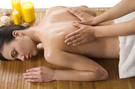 massage therapy: cute woman laying down on wood carpet with candle near getting an oil massage