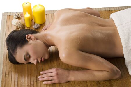 beautiful brunette relaxing herself in a spa with drops of water on her naked shoulder photo