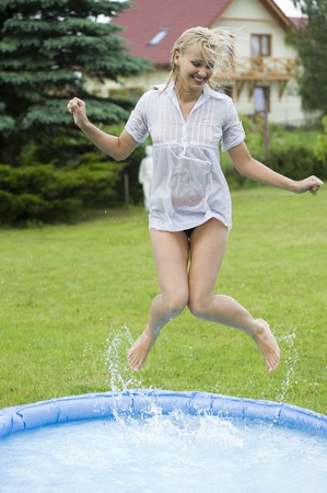 cute blond woman jumping inside a little swimming pool in a garden home photo