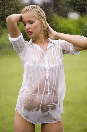 young sexy blond woman outdoor in a garden playing with sprayed water  with wet white shirt transparent  photo