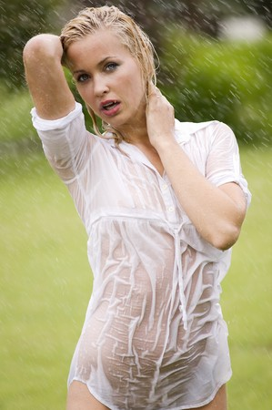 young sexy blond woman otodoor in a garden playing with water and rain with wet dress photo