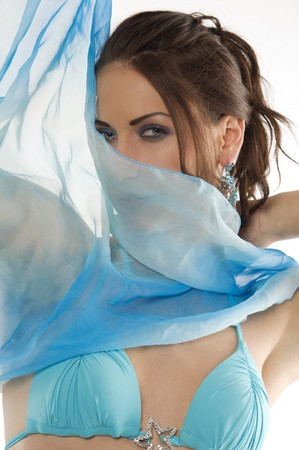 close up portrairt of a pretty brunette with blue-sky earring playing to hide her face with a summer headscarf  photo