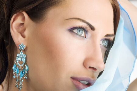 close up portrairt of a pretty brunette with blue-sky earring playing to hide her face with a summer headscarf Stock Photo - 7412210