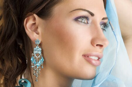 silk scarf: close up portrairt of a pretty brunette with blue-sky earring playing to hide her face with a summer headscarf  Stock Photo