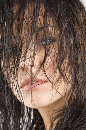 hair cover: portrait of a cute brunette with wet hair in front of face looking in camera