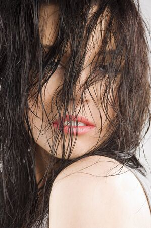 young and sensual brunette covering  face with wet long hair and looking in camera photo