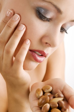 sweet beauty portrait of blond girl looking at some argan seeds on her hand photo