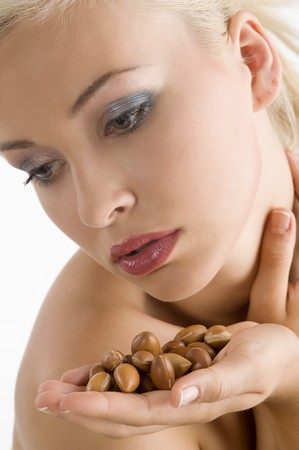 beauty shot: close up of blond cute woman in a beauty shot keeping some seeds of argan in hand looking down
