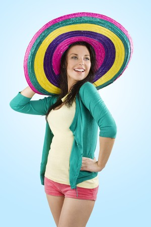 young and pretty brunette woman with colored dress and a big hat full color photo