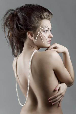 modelos desnudas: chica de moda elegante con creativa componen mostrando su hombro desnudo con un collar de perlas cayendo