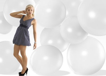 blond young woman wearing blue polka dot dress jewellery and taking pose photo