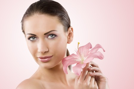 Fresh clear healthy portrait of young woman with pink lily and stunning blue eyes photo