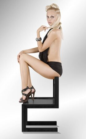 sexy shot of a blond woman with hair style sitting on a black chair photo