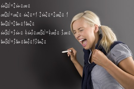 nice school girl in panic , screaming in front of the blackboard, during a math lesson photo