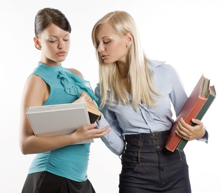two cute student girls looking at the same book talking  Stock Photo - 7635516