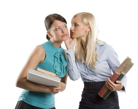 two nice girl blond and brunette with book like student one wishpering to the other Stock Photo - 7635488