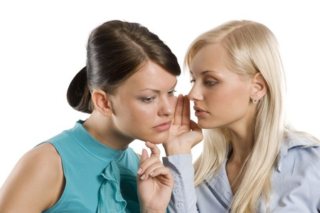 close up of a blond and a brunette girl wishpering as close friends Stock Photo - 7635517