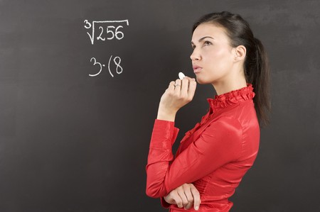 pretty young college student in act to think near a blackboard photo