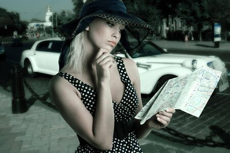 elegant woman in blue polka dot dress and hat looking at a tourist map  photo