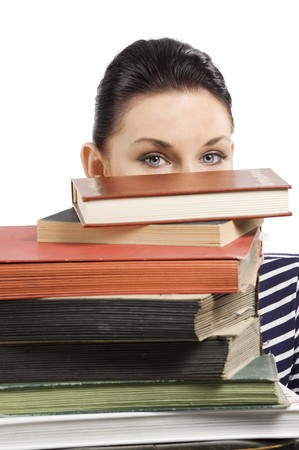 close up portrait of young and cute brunette student hiding her face behind a pile of books photo