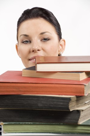 funny shot of a young brunette student coming up with face from a pile of book photo