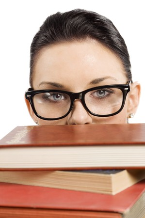 pretty student with big glasses playing and hiding her face behind a pile of book photo