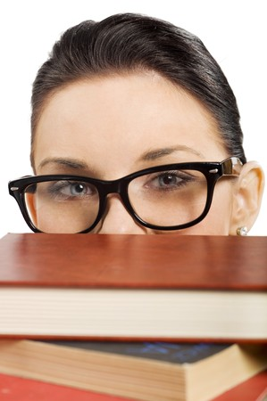 pretty student with big glasses coming up with her smiling eyes from a pile of book photo