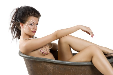 lying in bathtub: young woman with pearl on face and hair style inside a little old fashion bathtub