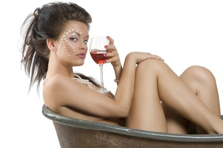 young  woman with pearl on face and hair style inside a little old fashion bathtub drinking a glass of red wine photo