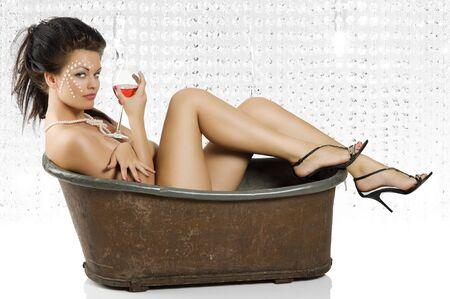 sexy schot van mooi meisje zit in een oude mode bad kuip met een glas rode wijn Stockfoto