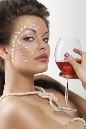 close up portrait of cute brunette with a glass of red wine and pearl on her face looking in camera Stock Photo - 8069268