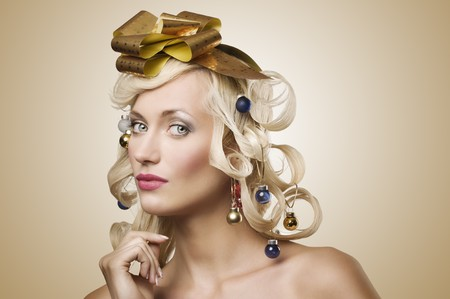 make a gift: fashion shot of a blond girl with curly hair stylish like a christmas tree with little noel decoration