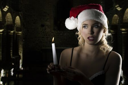 cute and attractive young woman with nightgown ant a christmas hat looking in the dark with a candle  photo