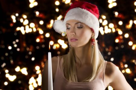beautiful young woman wearing a christmas hat and keeping a candle on dark background Stock Photo - 8191931