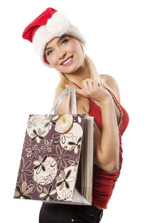 blond and cute woman with a christmas hat and a shopping bag looking in camera smiling photo