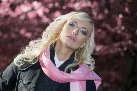 young blond woman with hairstyle wearing coat and scarf in a pink portrait outdoor photo