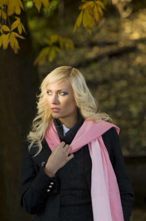 portrait of a beautiful young woman with a black coat and a pink scarf in a fall outdoor park photo