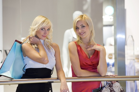 two young beautiful and elegant woman inside a commercial center go for shopping with bags photo