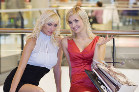 two blond beautiful girl in a commercial center with shopping bags looking in camera smiling photo