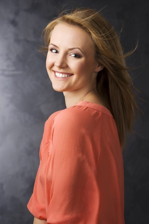 smiling blond girl on cdark background with orange shiirt and wind in her hair photo
