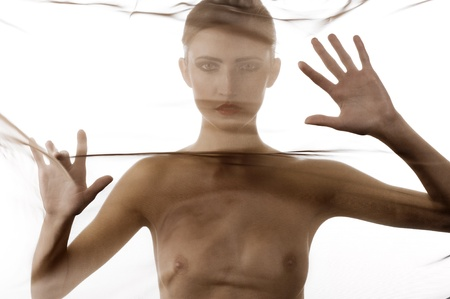 art fashion portrait of naked woman behind transparent material showing her breast Stock Photo - 8340103