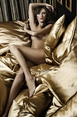 fashion sensual shot of a nude girl indoor laying between yellow golden pillow with hair style Stock Photo - 8392453