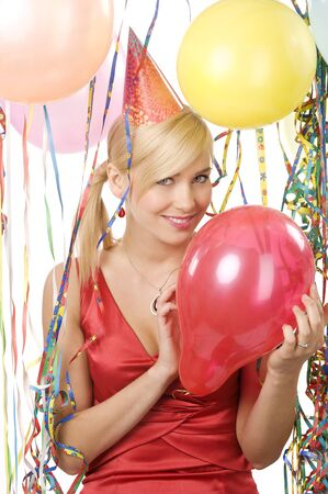 party balloons: blond young woman with funny hat keeping a red balloon in a party and looking in camera Stock Photo