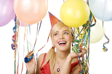 Pretty blond woman with funny hat and balloons during a party over white smiling and looking up photo