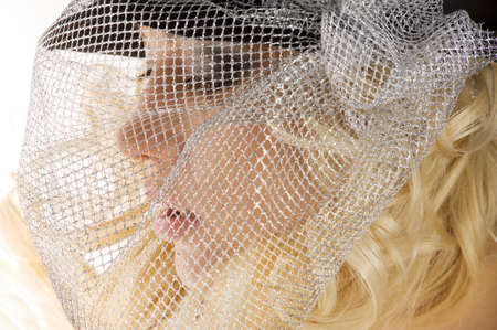 creative portrait of blond beautiful girl with hair style black hat and a silver net over her face  photo